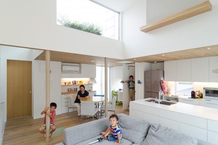 2 階のLDK は南側の開口のほかに、北側にハイサイドライト、東側にロフトの開口があり、天井が高いこととあいまって開放感 の感じられるつくり。奥の長男の立っているところにハシゴがあるが、ハシゴを使用しない時は扉を閉じることができる。