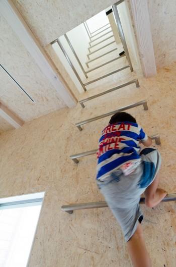 子ども部屋から2 階を通り抜けロフトへと至るハシゴ。壁はOSB による質感のある仕上げだ。