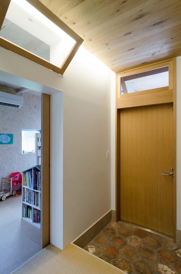 玄関には6 角形の古いテラコッタタイルを使用。光が行きわたるように玄関と子ども部屋の上部には窓が設けられている。