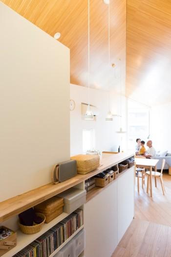 複雑なカットの高さのある天井が、空間を広く感じさせる。廊下に奥行きの浅い棚を設けるなど、収納も無駄なく設計。