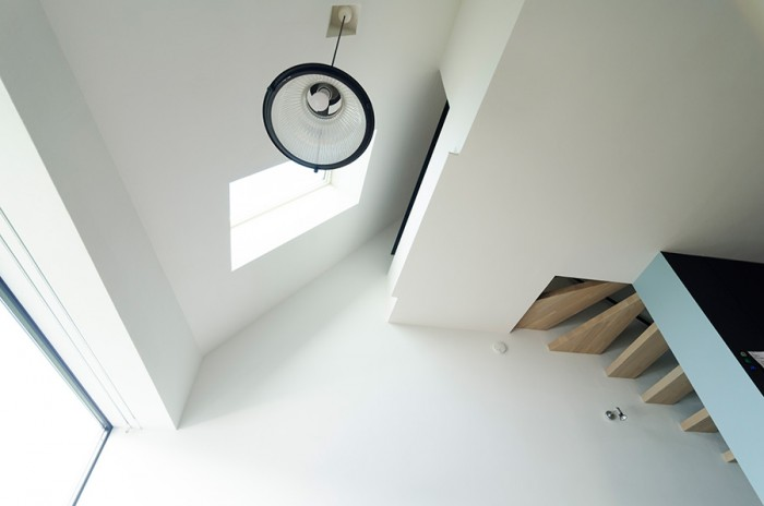 リビングから見上げる。斜めの屋根面にトップライトが設けられ、その屋根面と3階床がレベルがずれて接している。さらに階段側に3階と通じる孔が向けられて複雑な様相を呈している。