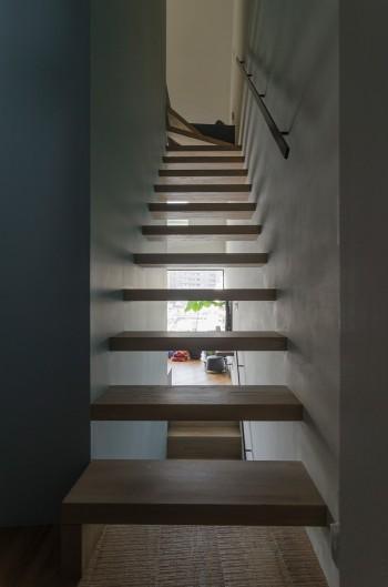 2階から階段を見る。踏板の間から外の景色が見える。