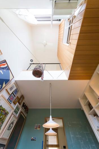 吹き抜けを見上げると、筋交いに鳥かごのオブジェが吊ってある。奥の壁には黒板塗料を自ら塗り、この家の1階のプランをチョークで描いた。