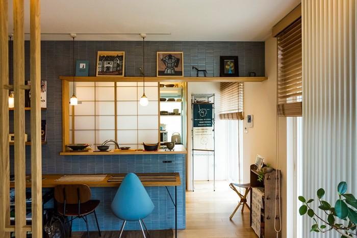 リビングからキッチンを見る。下がり壁にはディスプレイ棚を設け、山崎杉夫氏の作品を飾っている。料理や会話、団らんを楽しむキッチンは旭化成リフォームの「おうち居酒家」という仕様。
