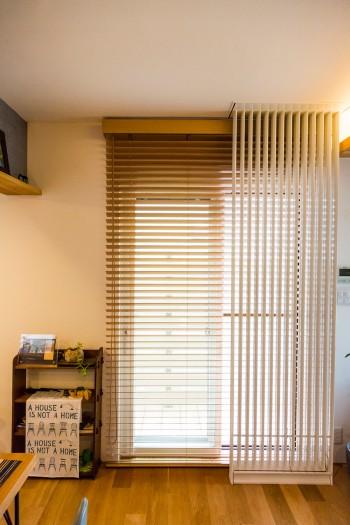 木製ブラインドの前の白い格子状のものは輻射熱を利用する冷暖房パネル。おだやかに室温を調える。