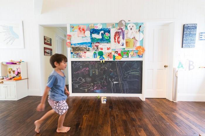 吹き抜けに面した広い踊り場は子どもたちのスペース。黒板の上には絵を貼れるボード、左側にはおままごとセット。