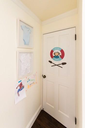 太陽くんの部屋のドア。左の額装されたベビー服は、子どもたちが生まれた時に病院を退院した時に着ていた服だそう。