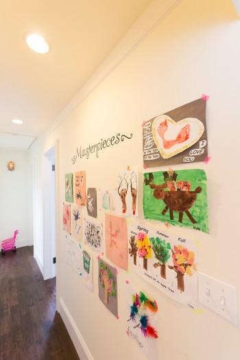 廊下の壁が画廊に早変わり。カラフルなテープで無造作に貼る。