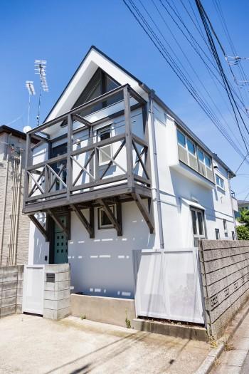 閑静な住宅街に建つ。三角屋根にウッドデッキが別荘風。