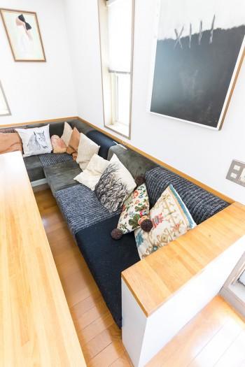パッチワークのように布を接ぎ合わせカバーを作ったソファー。壁の絵はデザイナー鎌田貴史さんの作品。「黒を取り入れたくてゆずり受けました」。