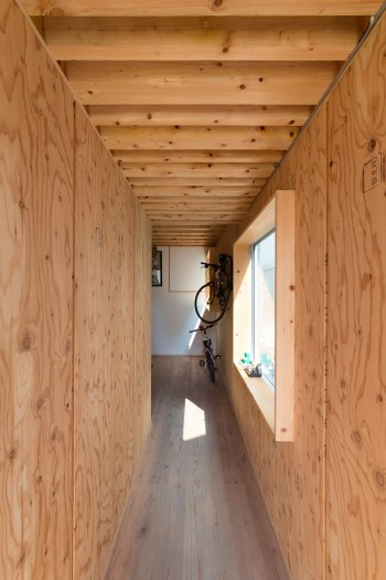 床までスギなどの無垢の木に囲まれた土間のような廊下が続く。窓枠はすべて奥行きを持ったフレームのような形状。