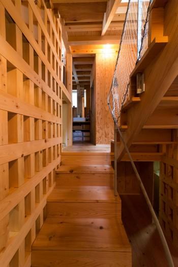 2枚の格子壁に囲まれた階段。すべての部屋を見通しながら、2階のリビングまでつながっている。