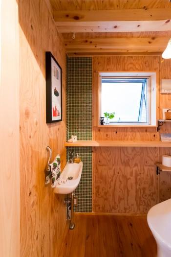 トイレにはモザイクタイルを貼付けた。お気に入りのイラストを額に入れて飾る。