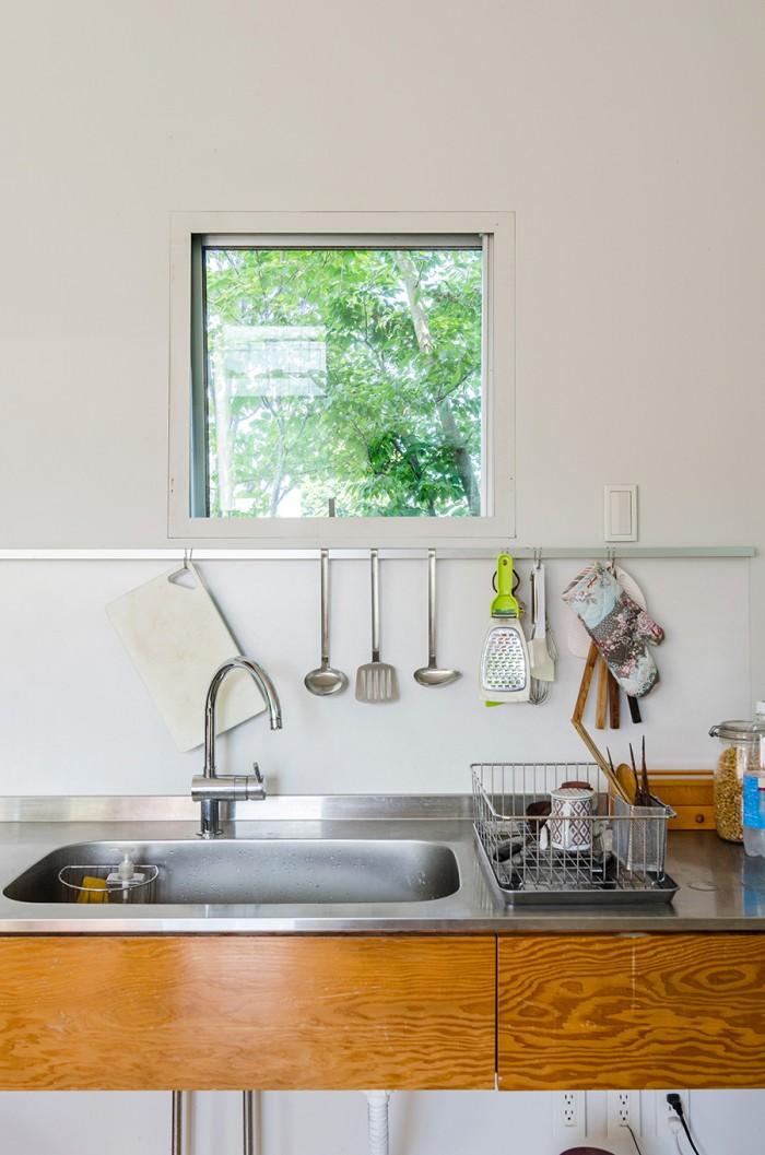 キッチンの壁につくられた小窓から外の緑を見る。