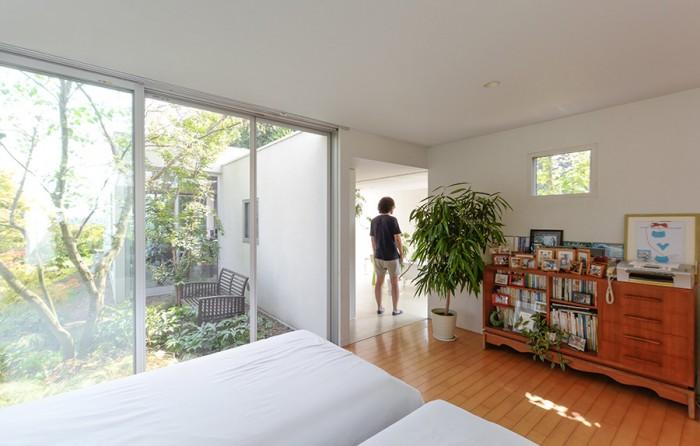 寝室から、バススペースに立つ健太郎さんを見る。庭を介して山﨑さんの部屋が見える。
