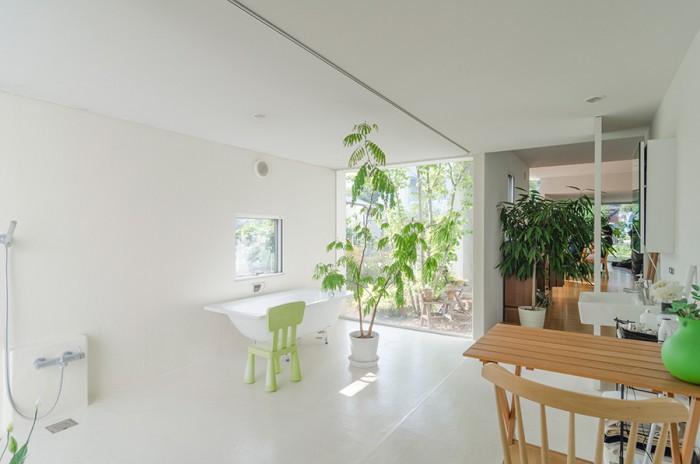 バススペース前から右手奥に玄関を見る。内部に仕切りがなく、また、庭とのレベル差がないということから内外が等価に感じられる。庭がインテリア的な感覚で接せられると同時に、家の内部に庭がいくつかある、そのような感覚もある。