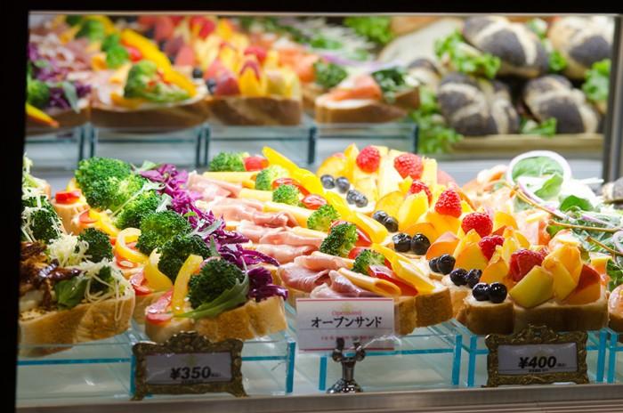 スライスした特製のパンの上に、スモークサーモンやホワイトアスパラ、ハムやチーズ、イチヂクやモモなどがたっぷりとのったオープンサンド 350円〜。(具材は日によって変更)