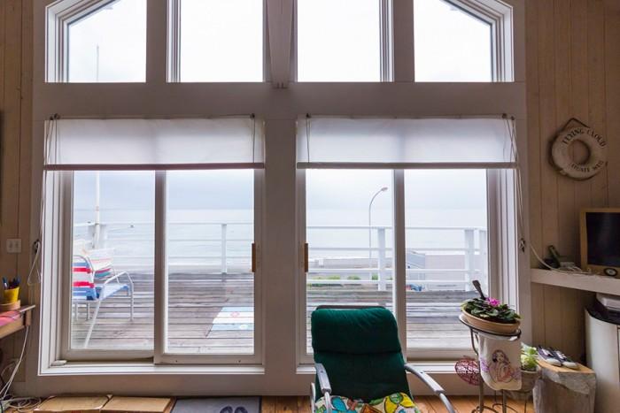 窓一面に広がる稲村ヶ崎の海。朝イチの波のチェックが至福の一時なのだとか。週に2〜3日はパドルボードで海に出ている。