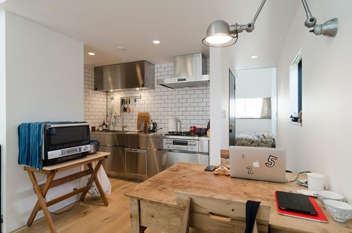 右奥に寝室。キッチンと1階の水回りには白いタイルを使用。このタイルはUさんのリクエストで、目地の色にまでこだわったという。