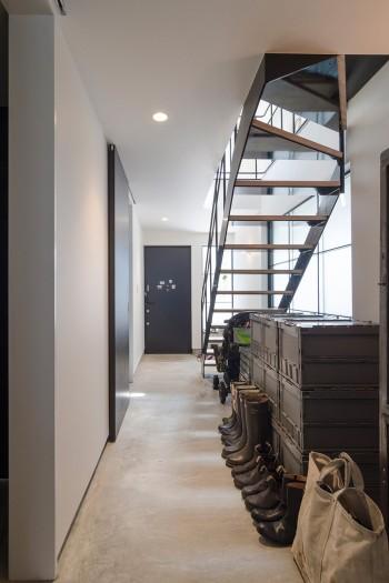 1階奥から玄関を見る。廊下にシューズがきれいに並ぶ。