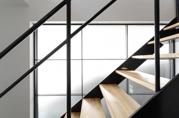 階段脇の大きなフィックスの開口からは外の擁壁に当たって反射した光が入ってくる。