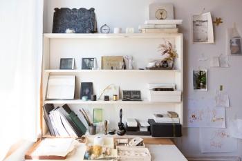 作業机の前の棚はモノトーン調。ひとつひとつへの愛着が感じられる。