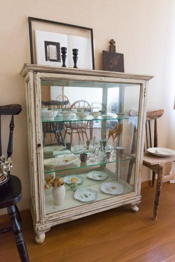 アンティークのキャビネットには、アスティエ・ド・ヴィラットのお皿などが。十字架の鍋敷きは金継ぎの先生の作品。