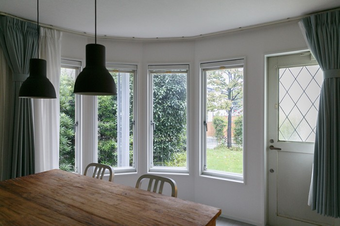 ダイニングから庭を見る。弧を描いて並ぶ窓が庭の風景を楽しく切り取る。庭にすぐ出られる扉もある。