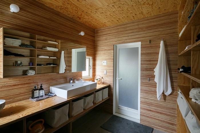 トイレと洗面はワンパッケージの広い空間に改修。大胆に壁面全面にLVL材をつかった。収納棚も同じ材なので、すっきりした印象。