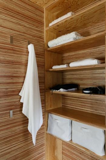 洗面スペースの棚はあえて扉をつけずに使い勝手をよくした。タオルフックは使わないときはたたまれる仕組み。