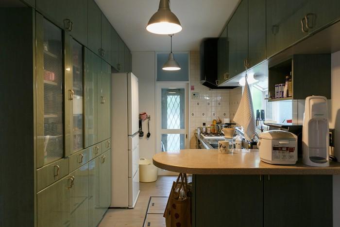 翡翠色が特長的なシステムキッチンも、コンロ周りのタイルも、既存のものを活かした。「収納がたっぷりで使いやすいです」(亜矢子さん)。