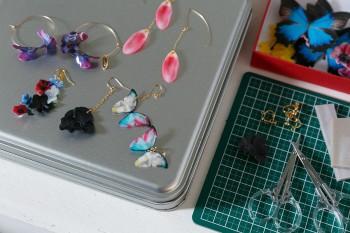 蝶々や花などの写真を布にプリントして樹脂で固めた亜矢子さんオリジナルアクセサリー。WEBショップで購入できる。