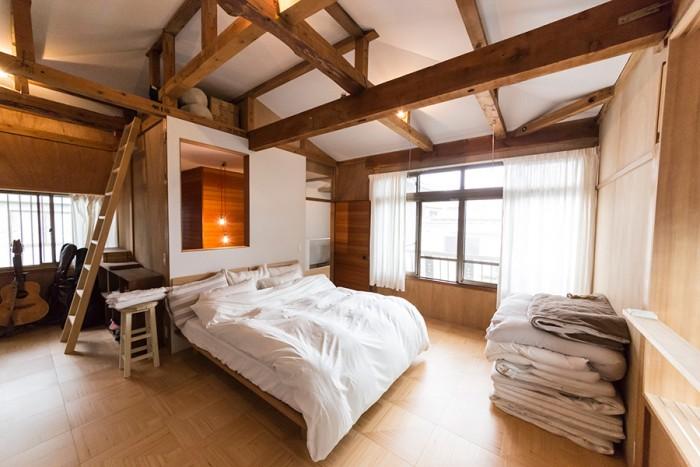 2階のベッドルーム。天井、壁の一部を白く塗った。ベッドヘッド上の壁の開口部から、風や光が1階まで通り抜ける。