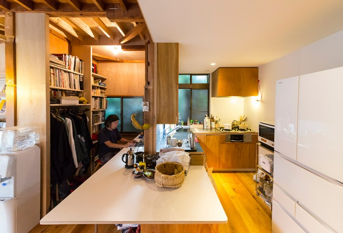 キッチンと英朗さんのワークスペースが、仕切りを挟んで隣接する。たくさんの本と、服を整理できるスペースも確保。