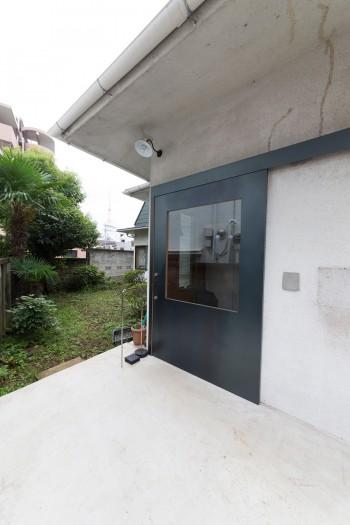 玄関の扉も、荷物の出し入れがしやすいよう、左右にスライドできる大きな引き戸に。奥には贅沢な広さの庭も。