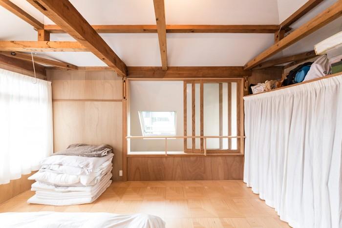 和室の名残りが残るベッドルーム。ガラス戸の向こうが吹き抜け部分。クローゼットは設けず、カーテンで仕切って押し入れだった部分を活用。こうしておくと自由度が高く、用途に合わせて後から変えられる。