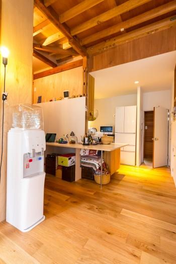 天井の荒々しい梁が印象的。キッチンからワークスペースにかけて設けたテーブルは、色々と活用できて便利。