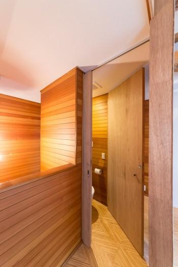 2階のトイレは狭さをクリアするため、ドアが2段階式に。廊下や階段はもとからあったはめ板を活かした。