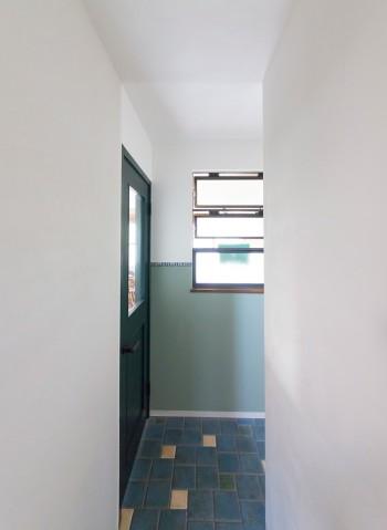 1階の廊下は白と落ち着いたブルーグリーンの組み合わせ。「家の中に窓を作るのが夢だったんです」と、さくらさん。