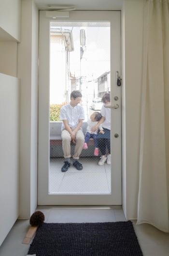 家の中から、玄関前のベンチに座る一家を見る。