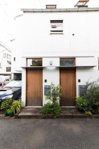 植栽が白い壁に映える玄関。もうひとつのドアは仕事仲間が使う別のスペース。