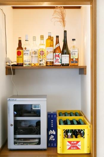 菜穂子さんが好きなお酒の瓶を並べた収納棚。「奥から酒瓶を照らす照明をつけてみました」(大介さん)。