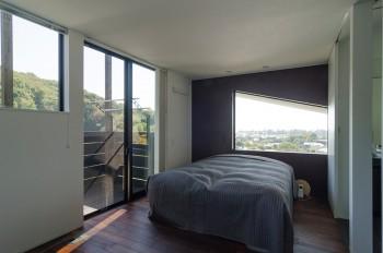 2階とは対照的にダークな色合いの壁と上辺を斜めにデザインされた開口が印象的な寝室。