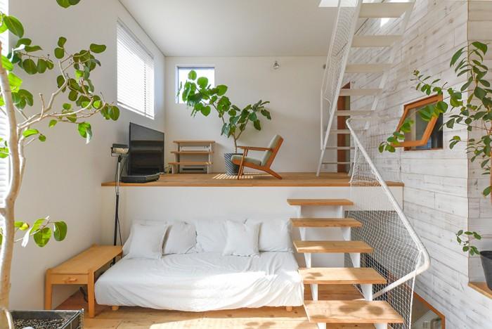 """3階の""""外""""の部分につくられたリビングは、スキップして2段構成になっている。左の外壁に開けられた開口は、枠を見せないデザイン。対して、""""家""""を囲う壁では木製サッシの枠を見せて色も塗っている。"""