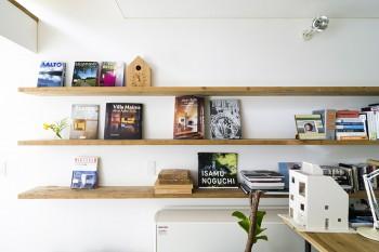 壁の棚には建築関係の本が並ぶ。