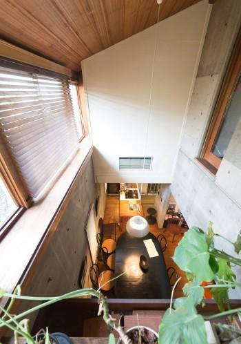 吹き抜けから、ペニンシュラキッチンとダイニングテーブルを見下ろせる。ここに床を張り、部屋にすることも可能だ。