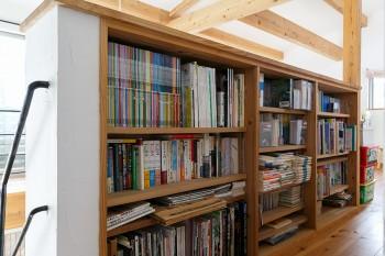 2階の吹き抜け周りにつくりつけられた書架は、家族3人でシェアして使う。