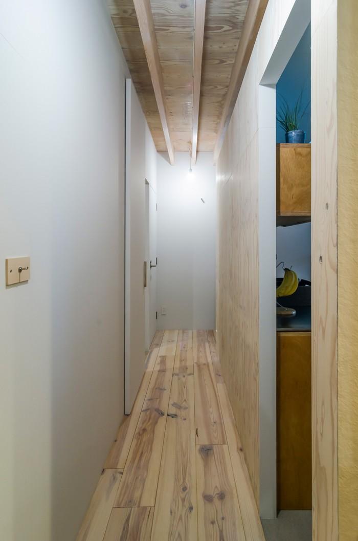 右がキッチン、左奥に寝室がある。突き当りを右に折れるとダイニングの空間。