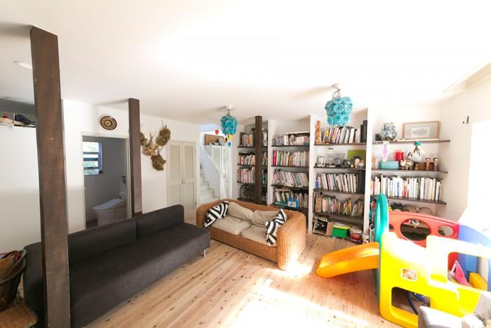 白い壁に、床は無垢の杉材で統一。以前は陳列棚だったところを本棚に。