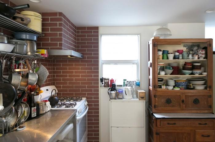 レンガ風のタイルが温かいキッチン。年代物の家具が似合う。
